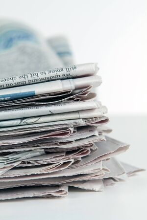 Stack of newspapers sit on a white background in vertical format. photo