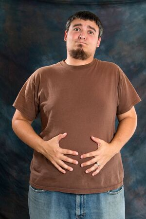 bloating: Overweight man holds his stomach because of discomfort caused by overeating and bloating.