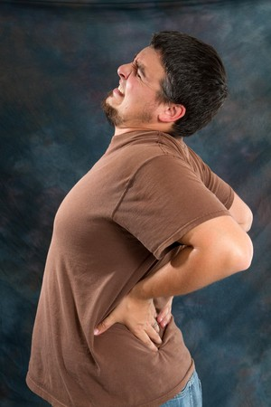 Man with back pain massages his back trying to relieve his backache. Stock Photo
