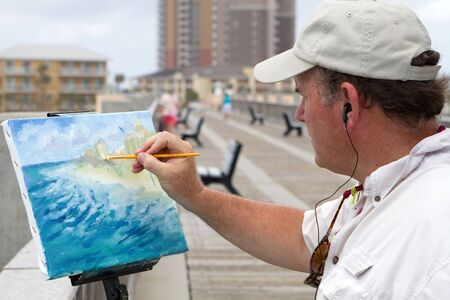 earphone: Artist standing on a pier and listening to music through earphones uses an angular brush to add highlights to a canvas mounted painting of the coast he is working on.