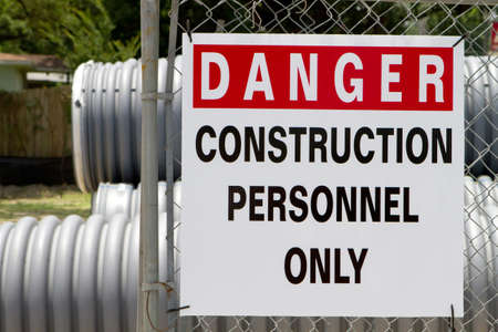 Danger Construction Personnel Only sign hangs on a chain link fence outside a construction site.