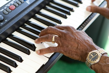 american music: Hands of an elderly african american man playing the keyboard.