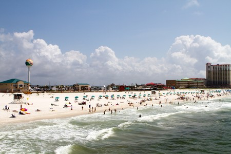 Tourists and vacationers sunbath and swim on Pensacola beach. Banco de Imagens