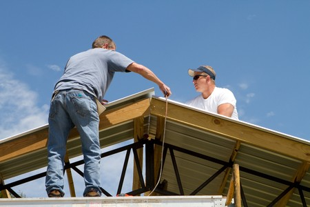 Roofing construction workers apply sheet metal to a barn roof. Stock Photo