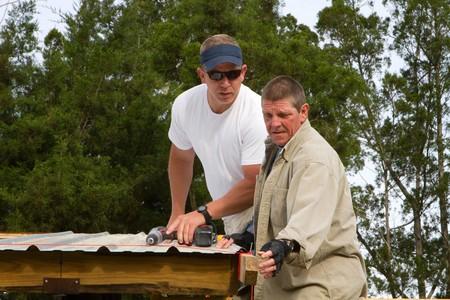 alineaci�n: Dos trabajadores de la construcci�n comprobar una l�nea recta para verificar la alineaci�n de un trabajo de techado.  Foto de archivo