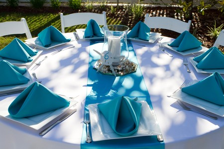 shadowed: Outdoor dinner table is setup with plate, silverware and folded napkins for a wedding reception.