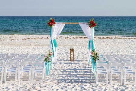 Bruiloft archway, stoelen en bloemen zijn gerangschikt op het zand ter voorbereiding van een strand huwelijks ceremonie.