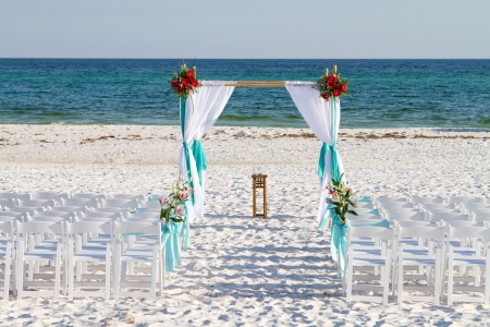 Wedding archway, chairs and flowers are arranged on the sand in preparation for a beach wedding ceremony.  Stock Photo