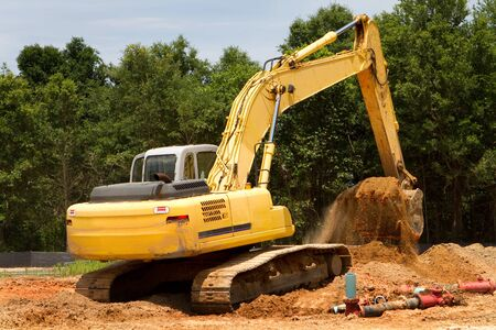 Backhoe machine uses shovel scooper to excavate and move dirt. Imagens