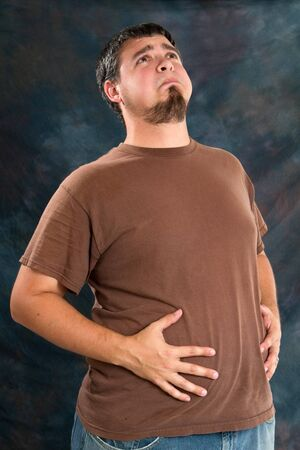 potbellied: Overweight man holds his stomach after eating too much resulting in indigestion.