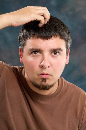 perplexing: Hombre rasca la parte superior de su cabeza y tiene un aspecto quizzical y cuestionamiento en su rostro.