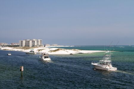 Charter fishing boats enter Destin Harbor, Florida. Stock Photo - 7356846