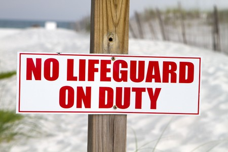 Sign posted at a beach notifies swimmers that there is no lifeguard on duty. photo