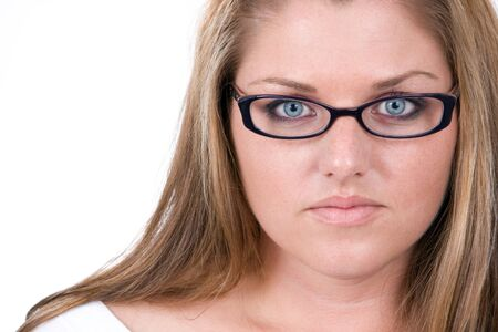 Close up on face of young business woman wearing glasses with a serious professional look.