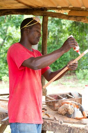 applies: Jamaican carpenter applies glue to a piece of cedar wood for a cabinet he is building.