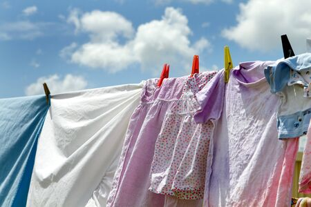 Childrens clothes and bedsheets have been hung out to dry on a clothesline viewed against a blue sky with clouds.