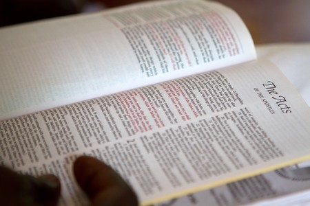 Black man's hand holds bible open to the gospel of Acts. Stock Photo - 7627549