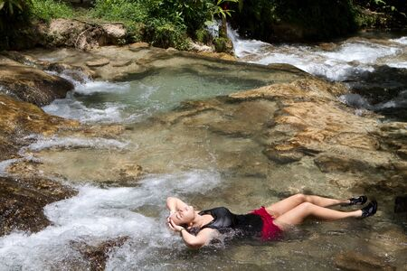 Young woman tourist relaxes in a shallow pool of water at the Dunn's River Falls in Jamaica. Stock Photo