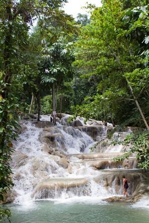 vacancier: Jeune femme touriste commence � monter Dunn River Falls en Jama�que.