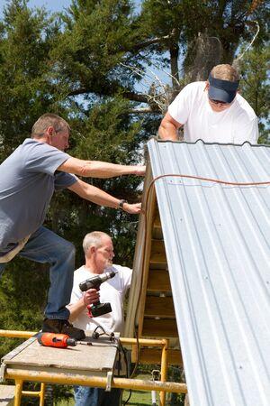 attach?: Equipo de trabajo de construcci�n se asienta sobre andamios para adjuntar hoja de metal a las vigas en el techo de un granero utilizando ca�ones de tornillo de alimentaci�n y ejercicios.
