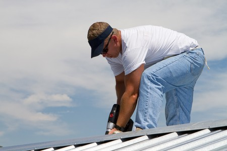 Construction worker uses a power drill to attach a cap the the top of a sheet metal roofing job with screws. photo