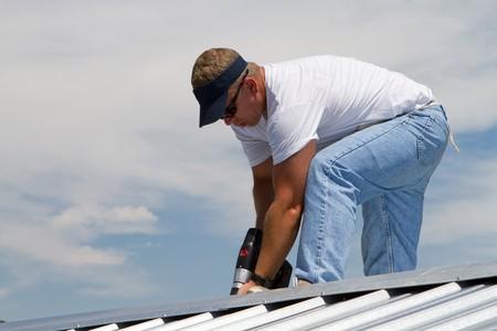 adjuntar: Trabajador de la construcci�n utiliza una taladradora para adjuntar una gorra el la parte superior de un trabajo de techado de chapa met�lica con tornillos.