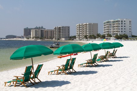 Tourists relax laying on the beach behind beach umbrellas and beach chairs with highrise condominiums in the background. Stock Photo - 7793809