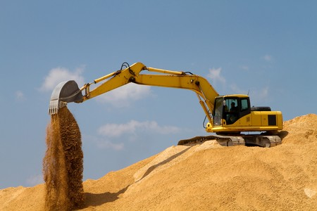 Excavator uses its bucket shovel to move piles of gravel. 版權商用圖片