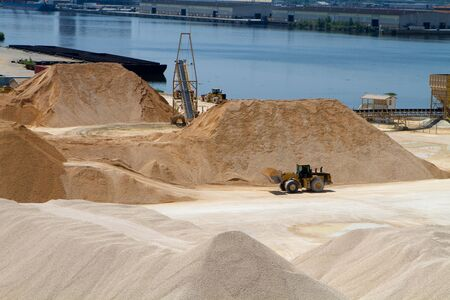Front end loader moves gravel at a gravel and materials storage operation plant by a river. photo
