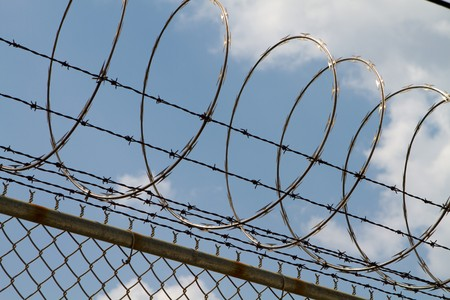 Razor wire and barbed wire top a fence to prevent people from climbing over.