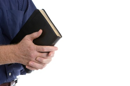 Missionary man holds his bible with interlocked fingers to pray. Stock Photo - 8169155