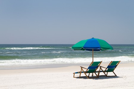Two beach chairs and an umbrella sit on the sand at Fort Walton Beach, Florida.