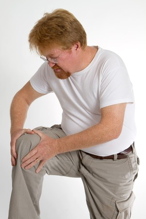 relieve: Man massages an old sport injury to relieve the pain. Stock Photo