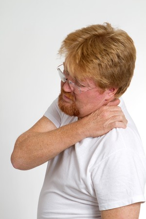 arthritic: Mature man massages and squeezes his shoulder in pain.