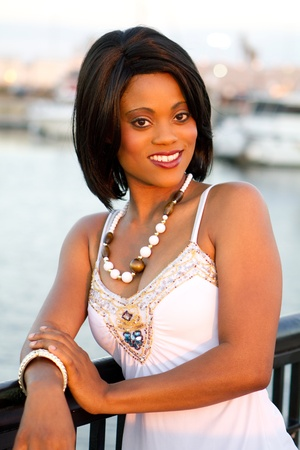 fashionably: Fashionably dressed business woman smiles at an outdoor water setting photographed by warm sunset light.
