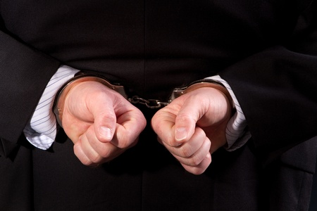 Close up of man wearing suit handcuffed behind his back. Stock Photo - 8678032