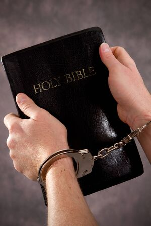 Handcuffed male hands hold a black Holy Bible. Banco de Imagens
