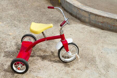 abandoned: Abandoned red tricycle with a yellow seat sits on concrete pad. Stock Photo
