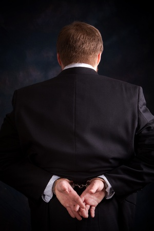 laundering: Businessman in suit is handcuffed behind his back.