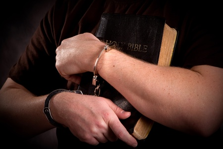 gospels: Criminal in handcuffs clutches his bible in prison ministry setting.