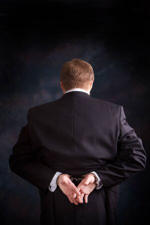 Man is arrested and handcuffed behind his back for white collar crime. photo