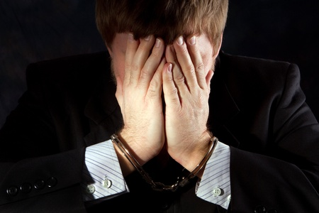 Handcuffs businessman covers his face to hid his identity from shame. Stock Photo