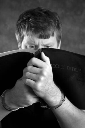 Prisoner finds comfort by studying the Holy Bible while in handcuffs. Stock Photo - 8776219