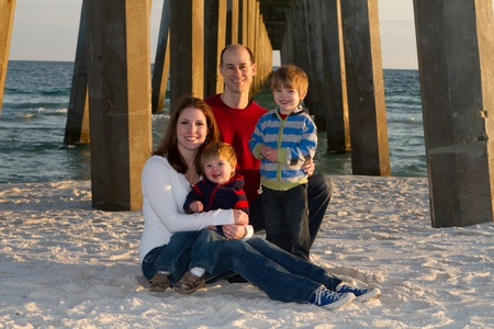 Young family poses for a beach portrait under a pier.