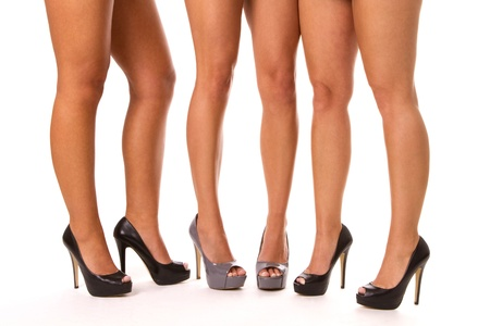 Close up of three womens legs in high heeled shoes. Фото со стока