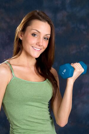 renforcer: Young slender woman uses a dumbbell to exercise and strengthen her biceps.