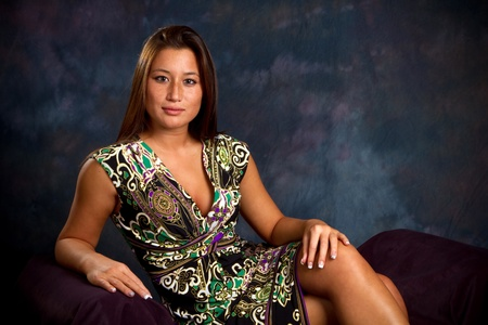Classy looking Asian American woman is in a seated pose. Imagens