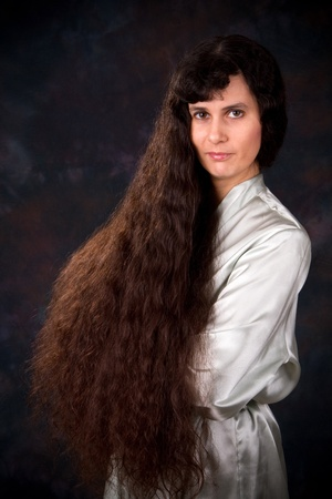 long: Extremely long haired Middle Eastern woman in a light blue robe poses in front of a dark background. Stock Photo