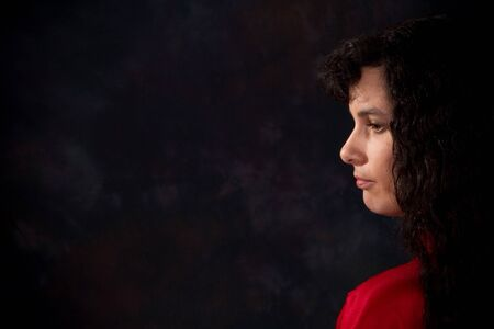 somber: Serious and somber looking woman against a dark background. Copy space on left. Stock Photo