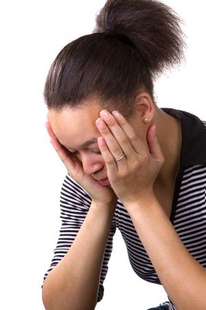 De Afrikaanse Amerikaanse vrouw houdt haar gezicht in haar handen in een staat van hopeloosheid en wanhoop. Stockfoto